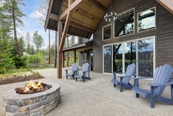 Classic rustic new home in dark grey wood exterior with forest landscape and back porch with pire pit and four chairs.