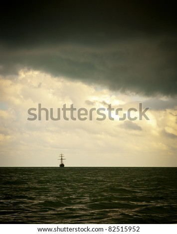 Classic sailing ship in the light of a huge storm