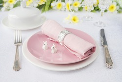 Classic serving for a Easter dinner with white and pink porcelain plates, pink napkin, silverware, two Easter rabbits and spring flowers are on a white tablecloth