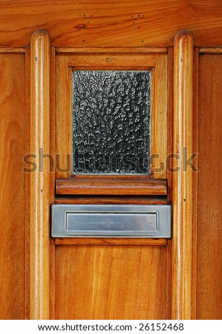 Classic shiny wooden door with silver colored mailslot or mailbox