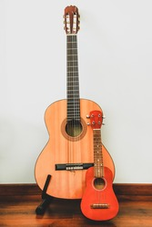 Classic six-string wooden guitar and Hawaiian four-string guitar Ukulele stand against the wall. Comparison of musical string instruments. Vertical image