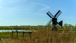 Classic small windmill in typical Dutch landscape