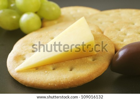 Classic snack cheddar cheese and crisp crackers with grapes and an olive on a black plate.