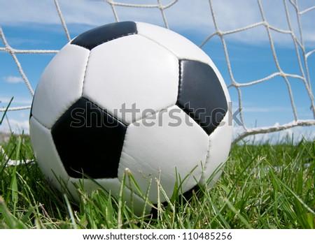 Classic soccer ball in the goal net against blue sky