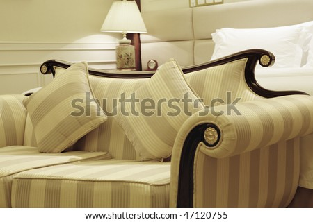 classic sofa in a stylish hotel room with bed and lamp in the background; high dynamic range image