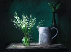 Classic still life with beautiful white Lily of the valley bouquet in glass jar and a white jar in ray of light. Green background. Art photography.
