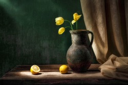 Classic still life with bouquet of three yellow tulip flowers in old vintage jug, two cut lemon fruits and drapery in beam of light on green background and old wooden table. Art photography.