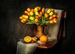 Classic still life with bouquet of tulips flowers placed in rustic wooden chair with fresh oranges and scarf
