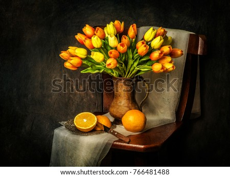 Classic still life with bouquet of tulips flowers placed in rustic wooden chair with fresh oranges and scarf  #766481488