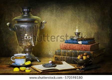 Classic still life with hot cup of tea placed with old samovar,fresh lemon, vintage books,nuts,cigar and illuminated candle on rustic wooden background.. Stok fotoğraf ©