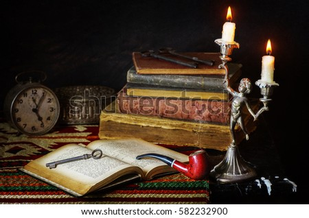Classic still life with vintage books placed with old clock,antique silver box,pipe,old keys and illuminated candles in copper antique candle stick.Knowledge is the key to success concept