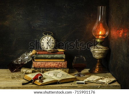 Classic still life with vintage books placed with old lamp,clock,letters and bottle of fresh drink on rustic wooden background.
