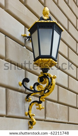 Classic street lantern with gold details on brick wall