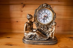 classic style table clock with bronze sculptures of a woman and a child, on wooden background