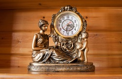 classic style table clock with bronze sculptures of a woman and children, on wooden background