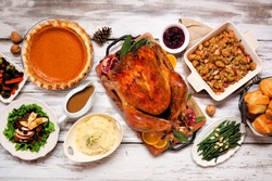 Classic Thanksgiving turkey dinner. Overhead view table scene on a rustic white wood background. Turkey, mashed potatoes, stuffing, pumpkin pie and sides.