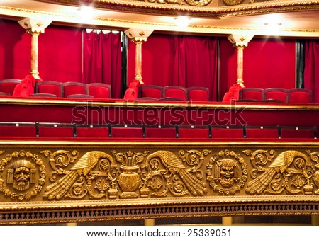 classic theater balcony with red chairs and golden details
