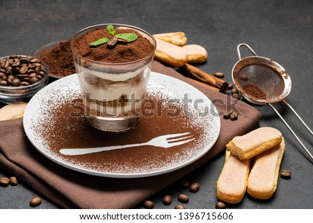 Classic tiramisu dessert in a glass and cup of coffee on dark concrete background Photo stock ©