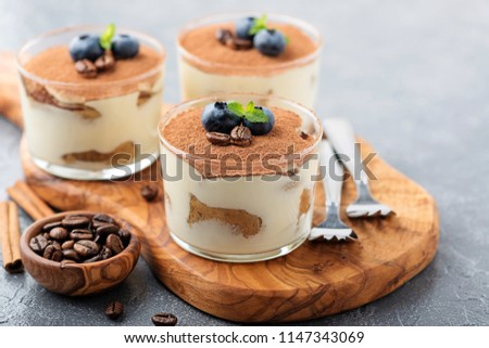 Classic tiramisu in a glass  on a gray background.