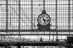 Classic train station clock hanging onto the roof of the old train station in black and white photography