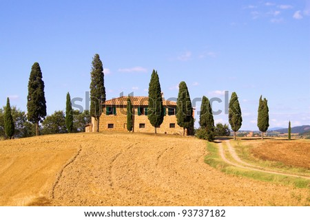 Classic Tuscan landscape with stone house and row of cypress trees