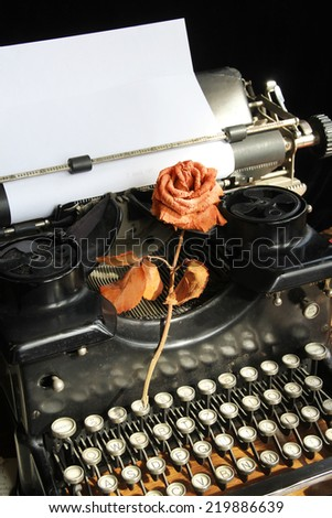 Classic type writer with blank paper and a withered rose