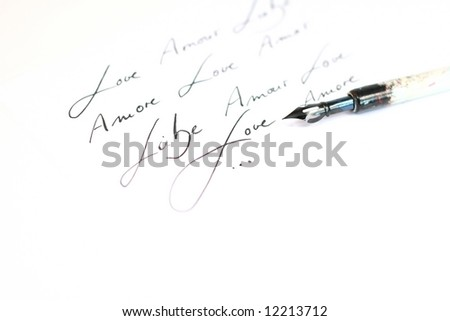 Classic used ink feather with heandwriting. Words: Love, Liebe,Amour,Amore on white background.