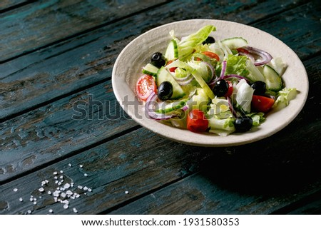 Classic vegetable salad with tomatoes, cucumber, onion, salad leaves and black olives in white ceramic plate. Dark wooden table. Сток-фото ©