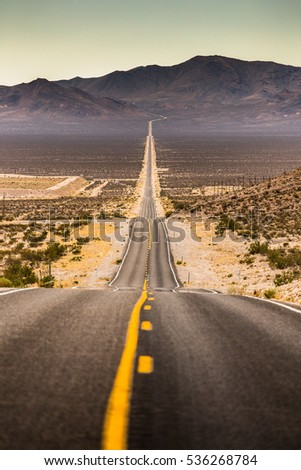 Classic vertical view of an endless straight road running through the barren scenery of famous Death Valley with extreme heat haze on a beautiful sunny day with blue sky in summer, California, USA #536268784