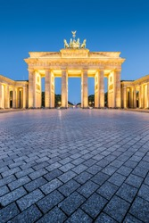 Classic vertical view of historic Brandenburg Gate, Germany's most famous landmark and a national symbol, in post sunset twilight during blue hour at dusk in summer, central Berlin, Germany