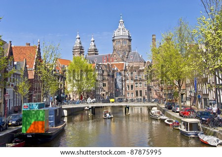 Classic view of Amsterdam. View from the canal to the church against the blue sky. Urban landscape in Amsterdam.