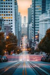 Classic view of downtown San Francisco with famous Oakland Bay Bridge illuminated in first golden morning light at sunrise in summer, San Francisco, California, USA