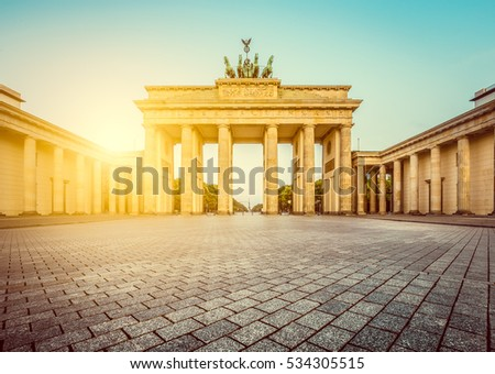 Classic view of famous Brandenburg Gate, one of the best-known landmarks and national symbols of Germany, in beautiful golden morning light at sunrise with retro vintage filter effect, Berlin, Germany
