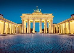 Classic view of famous Brandenburger Tor (Brandenburg Gate), one of the best-known landmarks and national symbols of Germany, in twilight during blue hour at dawn, Mitte district, Berlin, Germany