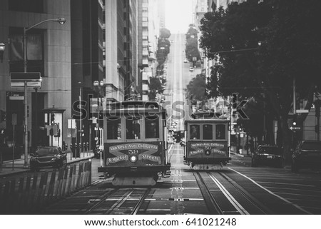 Classic view of historic traditional Cable Cars riding on famous California Street in beautiful morning light at sunrise in summer with retro vintage B&W filter effect, San Francisco, California, USA