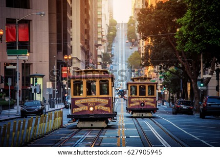 Classic view of historic traditional Cable Cars riding on famous California Street in morning light at sunrise with retro vintage style cross processing filter effect, San Francisco, California, USA #627905945