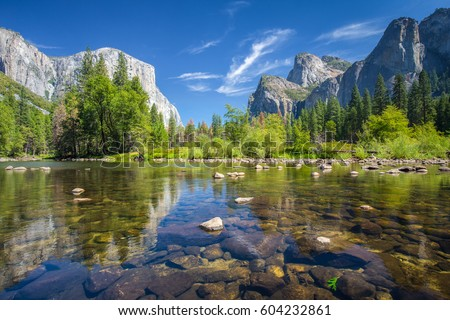 Classic view of scenic Yosemite Valley with famous El Capitan rock climbing summit and idyllic Merced river on a sunny day with blue sky and clouds in summer, Yosemite National Park, California, USA