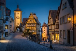 Classic view of the medieval town of Rothenburg ob der Tauber illuminated in beautiful evening twilight during blue hour at dusk, Bavaria, Germany