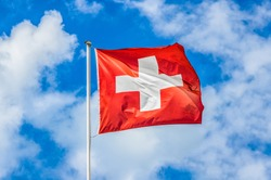 Classic view of the national flag of Switzerland waving in the wind against blue sky and clouds on a sunny day in summer on the First of August, the national holiday of the Swiss Confederation