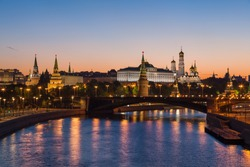 Classic view to the Moscow Kremlin and Bolshoy Kamenny Bridge above the river at half an hour before dawn with blue sky and bright orange horizon