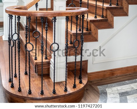 Classic vintage elegant wooden staircase with wrought iron railing. #1197427201