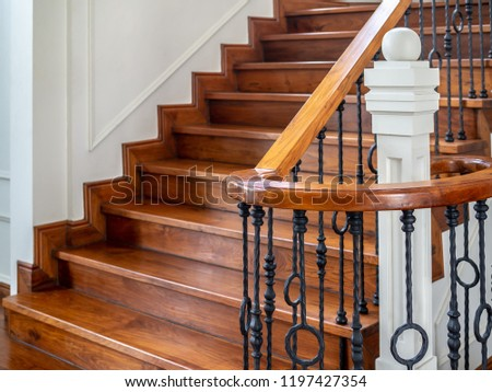 Classic vintage elegant wooden staircase with wrought iron railing. #1197427354