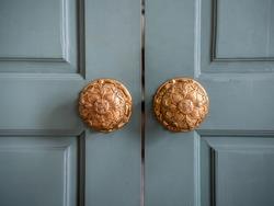 Classic vintage golden door knobs. Antique door knobs with carvings on wooden door.
