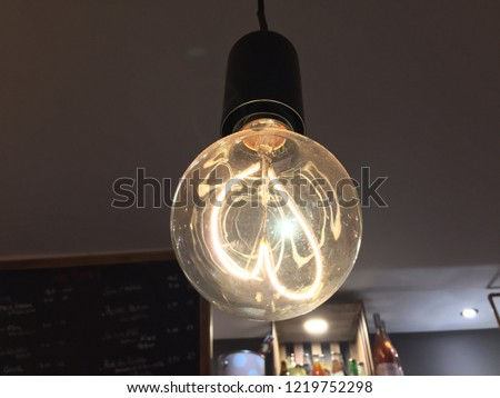 Classic Vintage Incandescent Lightbulb hanging from ceiling