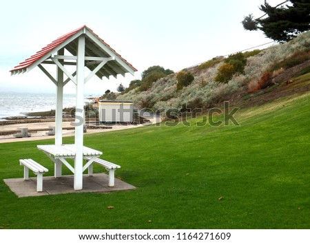 Classic vintage pic nic table bench with a red roof in a green park