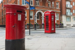 Classic vintage red phone booth and postbox on the street of London