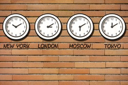 Classic wall clocks for different timezones on wall of bricks