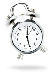 Classic white alarm clock ringing at six o'clock, isolated against a white background