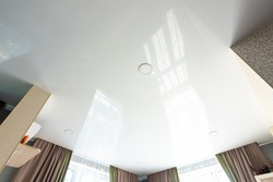Classic white glossy ceiling with recessed spotlights