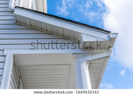 Classic white gutter system that collects water shedding off the roof, with slip connector, end cap, elbow tube, gutter hanger, gutter drop connecting  the outlet to the downspout with soffit, fascia Stock photo ©